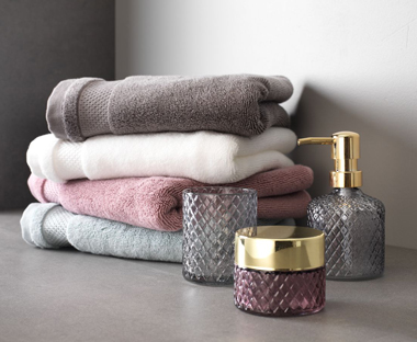 Pink and grey luxury bathroom accessories with soft 100% cotton towels.