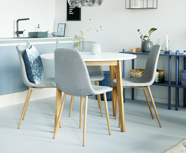 Grey fabric and wood dining chairs with white and oak round dining table