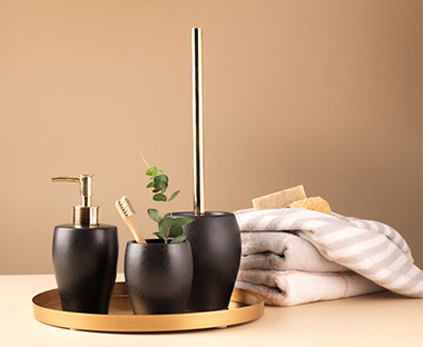 Stylish black and gold toilet brush with matching accessories.