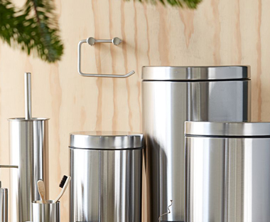 Stainless steel metal bathroom pedal bin with matching accessories.