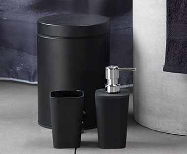 Chic matte black matching bathroom accessory set made from easy to clean plastic, toothbrush holder, pedal bin and soap dispenser.
