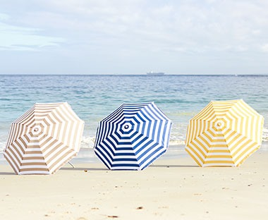 Striped parasols in yellow, blue or grey with adjustable height