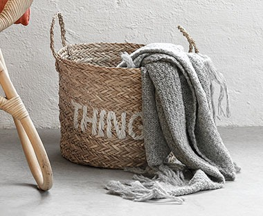 Grey soft throw in brown round basket