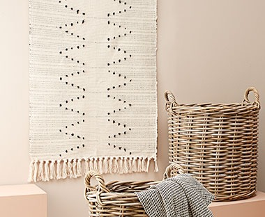 Handmade woven rug with tassel ends in cream and white pattern