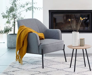 Comfortable grey fabric armchair.