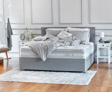 Double spring mattress on a grey fabric divan base with headboard