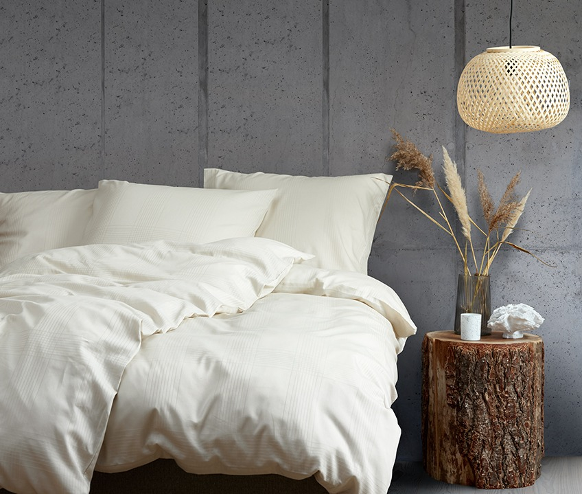 Elegant bedroom with a calm Nordic look and bed made with sand coloured bedding