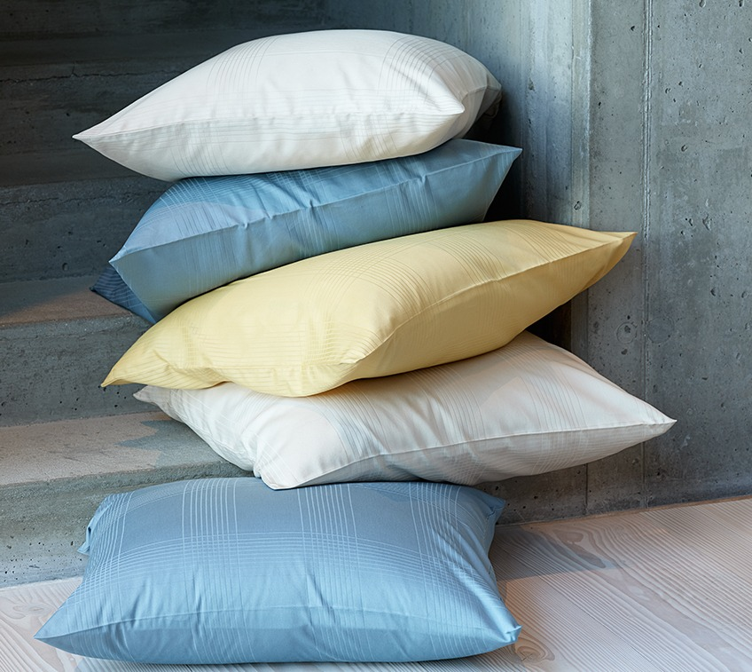 Pile of pillows with covers on petrol, sand and yellow