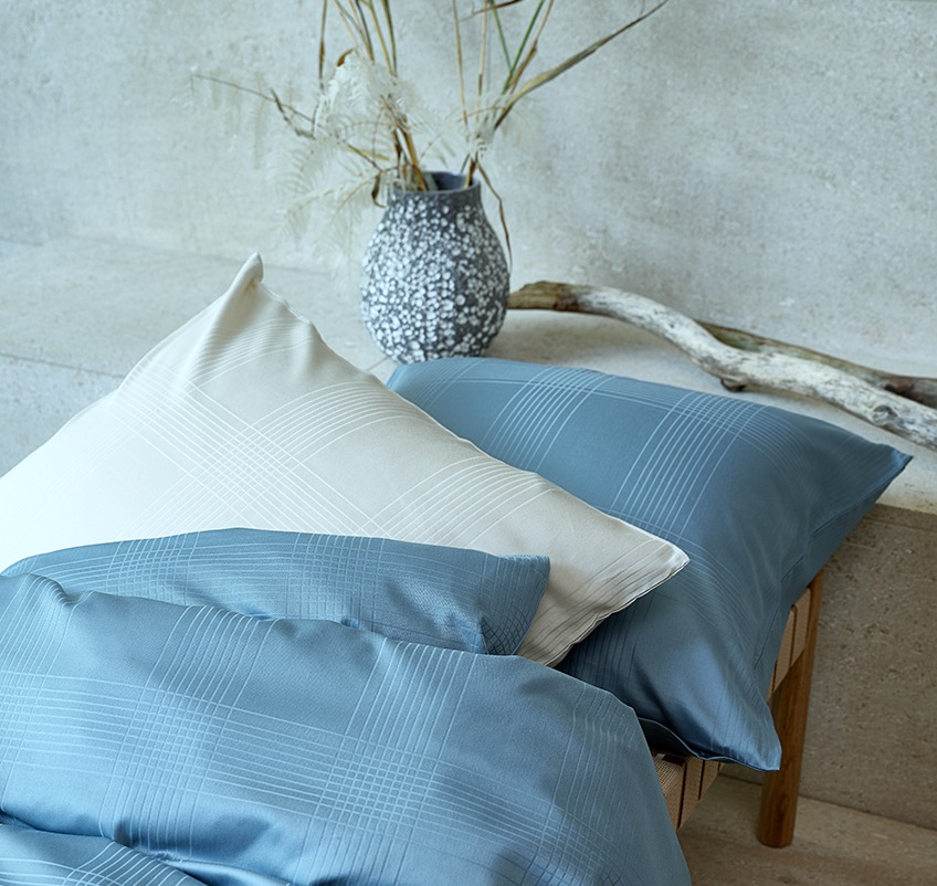 Pillow and duvet with luxury bed linen in petrol and sand