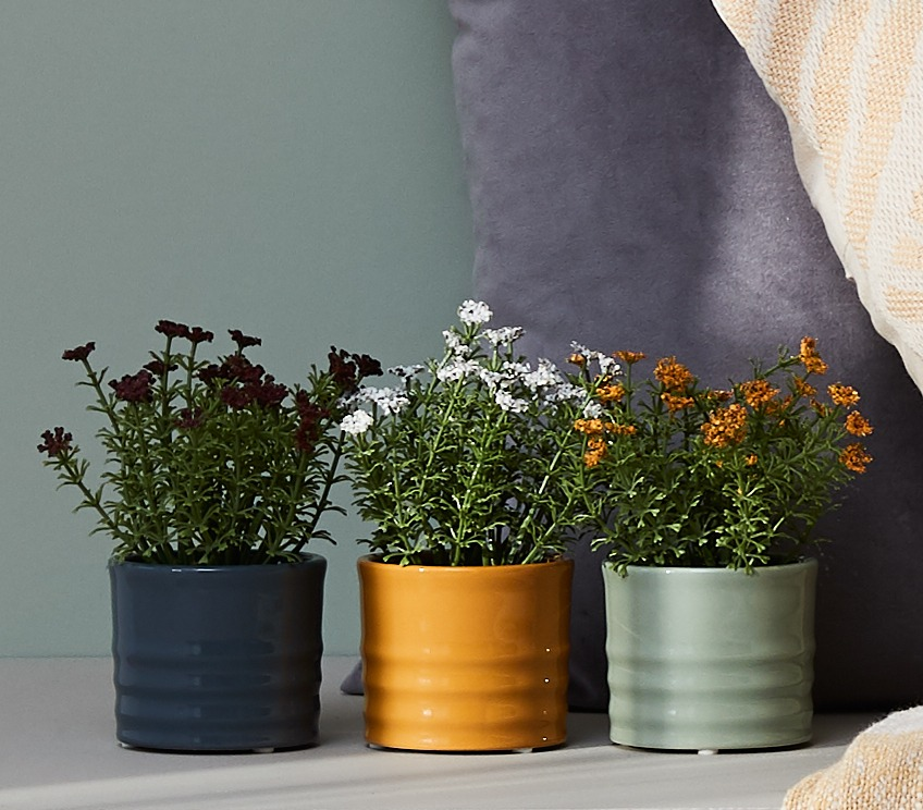 Faux flowers in different colours in blue, yellow and grey, yellow and green plant pots