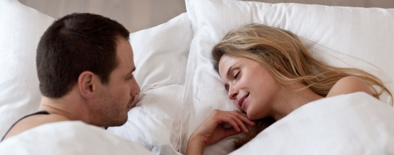 Man looking at happily sleeping partner