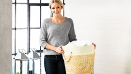 Woman holding washing basket filled with duvets and bed with a pillow, duvet, mattress topper