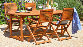 Brown rectangle outdoor table with wooden chairs with FSC label in bright garden