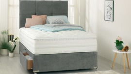mullti colour cushions and blue duvet covers on top of grey base with white and black foam mattress