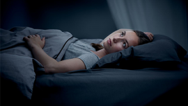 Woman sleeping in dark bedroom with duvet, pillow and mattress